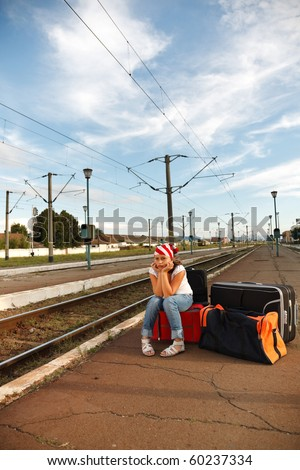 Young girl sitting on luggage and waiting for train in the station