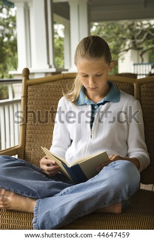 Young girl sitting on porch reading book.  Vertically framed shot. - stock photo