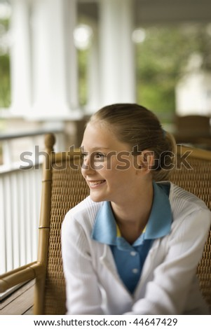 Young girl sitting on porch smiling looking off to the side - stock photo