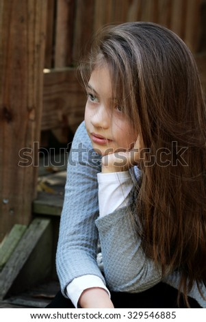 Young girl sitting on porch steps with long hair falling loosely around her face. Extreme shallow depth of field. - stock photo