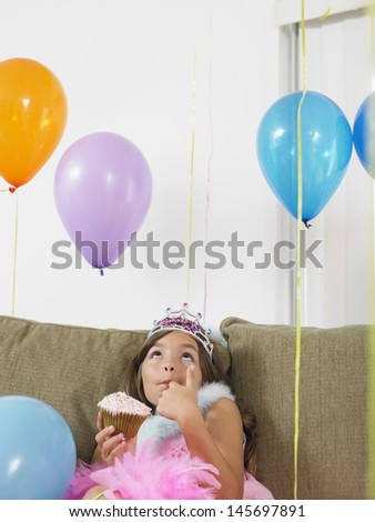 Young girl sitting on sofa and looking up at balloons with cupcake - stock photo