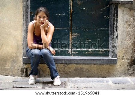 Young girl sitting on steps at home - stock photo