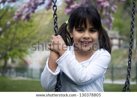 Young girl sitting on swing, smiling, portrait - stock photo