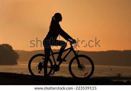 Young girl sitting on the bike by the river at sunset, - stock photo