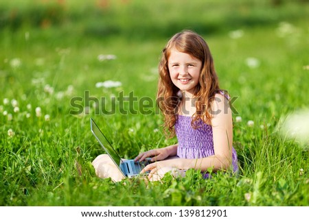 Young girl sitting on the grass and browsing through her laptop - stock photo