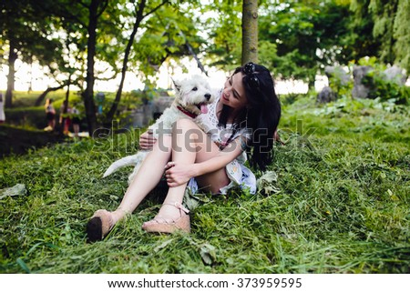 young girl sitting on the lawn with her dog - stock photo