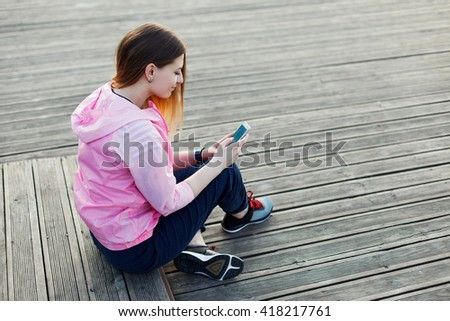 Young girl sitting on the pier and rewritten with her smartphone