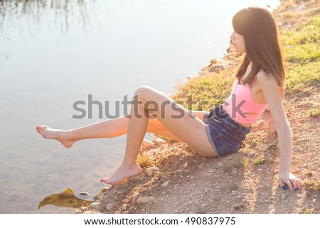 young girl sitting on the shore of a pond at sunset