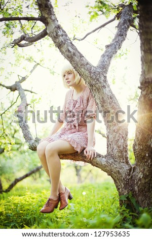 Young girl sitting on the tree branch in the spring garden - stock photo