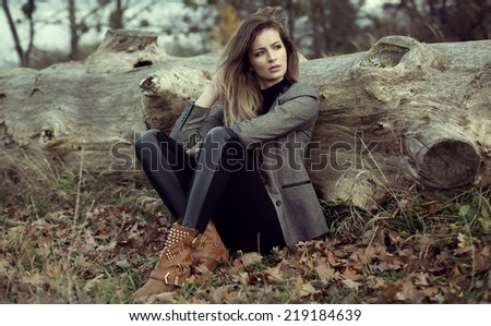 Young girl sitting outdoor in autumn scenery - stock photo