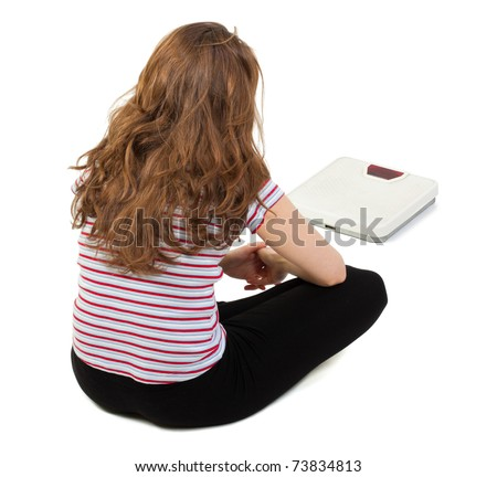 Young girl sitting sadly on the floor and looking at the scale in front of her, isolated on white.