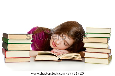 Young girl sitting ?t th? d?sk and sleeping on a book. Isolated on white background