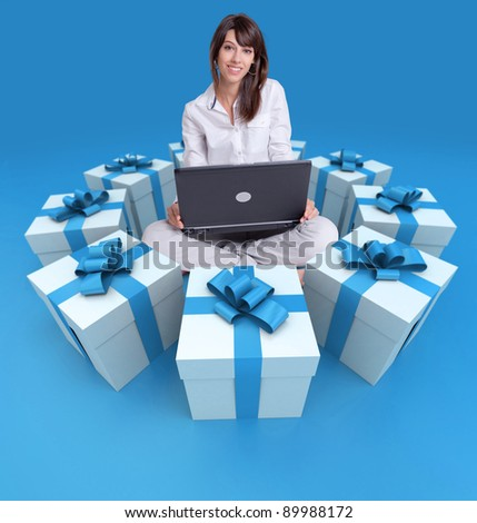 Young girl sitting with a laptop surrounded by gift boxes - stock photo