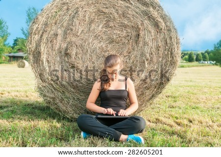 Young girl sitting with tablet  close to haystack in meadow - stock photo