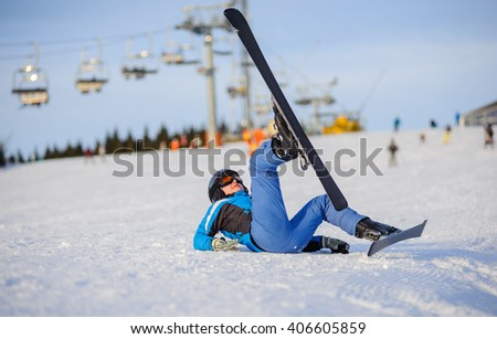 Young girl skier in blue ski suit after the fall on mountain slope against ski-lift. Ski resort at Carpathian Mountains, Bukovel, Ukraine. Winter sports concept.  - stock photo