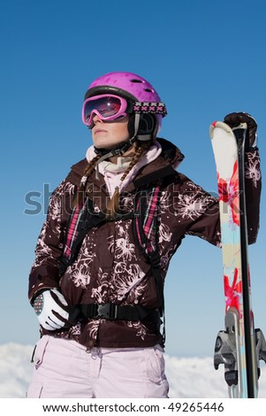 Young girl skier with skis wearing sport gear. Winter vacation - stock photo