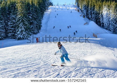 Young girl skiing downhill on a slope with other skiers on background