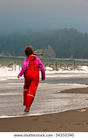 young girl skipping down beach shore - stock photo