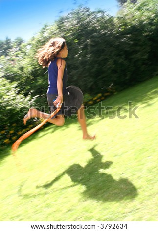 Young girl skipping with her rope, fast across the field on a lovely summer's afternoon, with lots of movement. - stock photo
