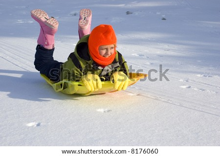 Young Girl Sledding on Snow Covered Lake - stock photo