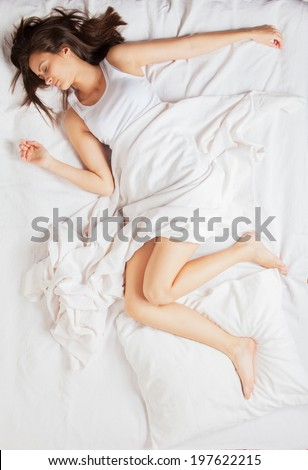 Young girl sleeping in bed, shot from above - stock photo