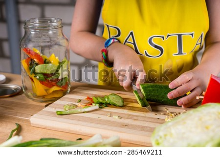 Young girl slicing dill cucumber for bottling with assorted fresh vegetables in a glass jar, close up of her hands