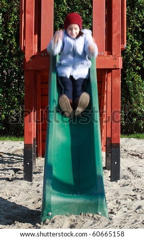 Young girl sliding on playground slide with motion blur - stock photo
