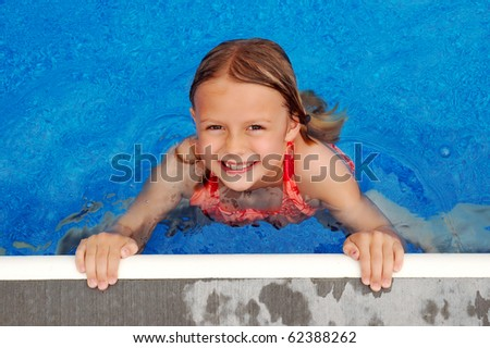 Young Girl Smiles at Side of Pool - stock photo