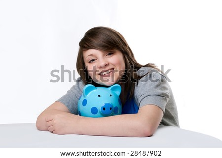 young girl smiling and hugging blue spotted piggy bank. Isolated on white background