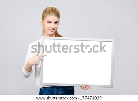 Young girl smiling and pointing to a white blank board. Beautiful young blonde girl in white shirt presenting. - stock photo