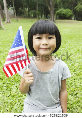 Young girl smiling and waving American flag outside