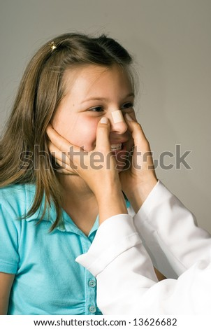 Young girl smiling as she has a band-aid applied to her nose. She is happy to be taken care of. Vertically framed photograph - stock photo