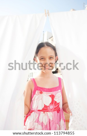 Young girl smiling at camera and holding white bed sheets while they dry hanging on a terrace.