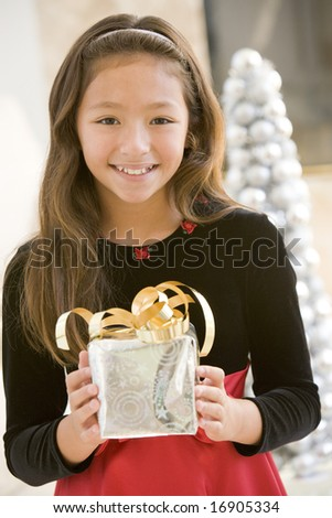 Young Girl Smiling,Holding Christmas Gift - stock photo