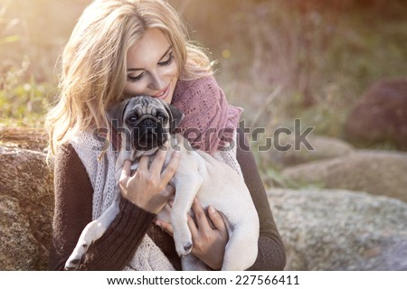 Young girl smiling in autumn scenery with pug dog  - stock photo