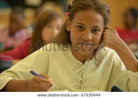 Young girl smiling in classroom - stock photo