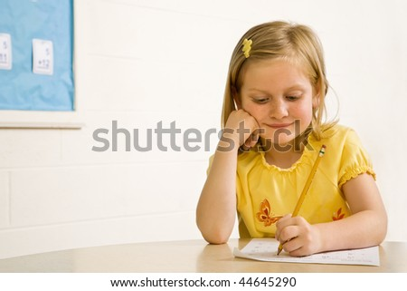 Young girl smiling in classroom writing on paper. Horizontally framed shot. - stock photo