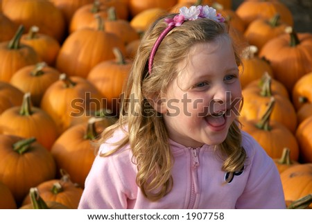 Young Girl smiling in pumpkin field - stock photo