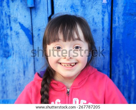 Young girl smiling on background of the blue wall. - stock photo