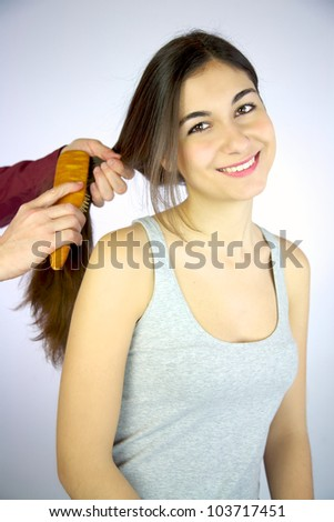 Young girl smiling while hairdresser brushes her long silky hair
