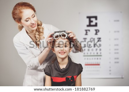 Young girl smiling while undergoing eye test with phoropter - stock photo