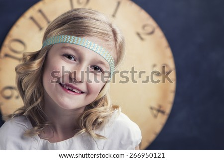 Young girl smiling with a large vintage clock behind her - stock photo