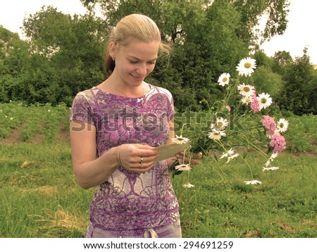 Young girl smiling with letter in her hands and a bouquet of wildflowers. Light Sepia - stock photo