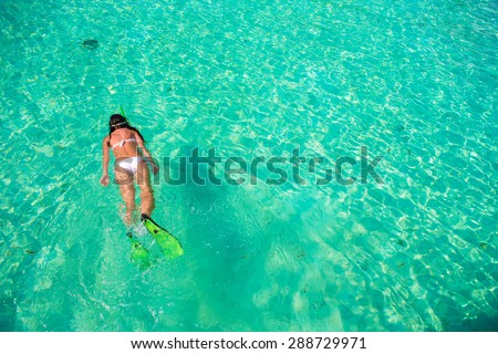 Young girl snorkeling in tropical water on vacation - stock photo