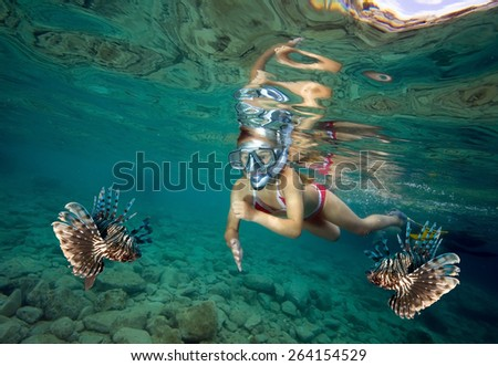 Young girl snorkeling with lionfish - stock photo