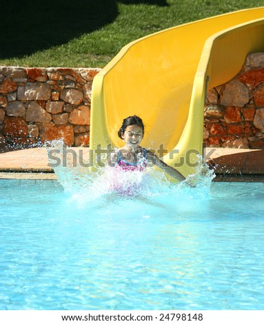 Young girl splashes at the end of a slide in swimming pool