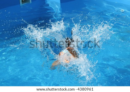 Young girl splashing and playing in a pool