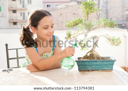 Young girl spraying water with a bottle onto a bonsai tree while sitting at a table on a city terrace.