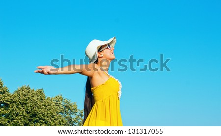 Young girl spreading hands with joy and inspiration - stock photo