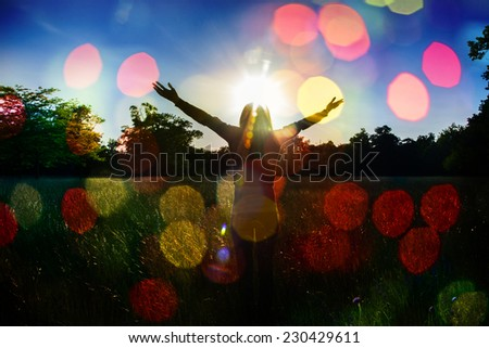 Young girl spreading hands with joy and inspiration facing the sun,sun greeting,colorful bokeh ,freedom concept,bokeh woman  young liberty background - stock photo